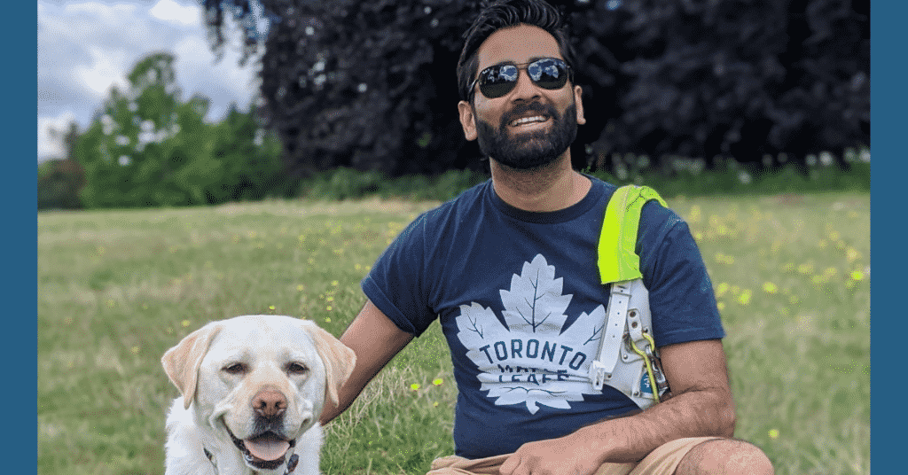 Guide Dog Kika and Dr Amit Patel sit on the grass with trees in the background